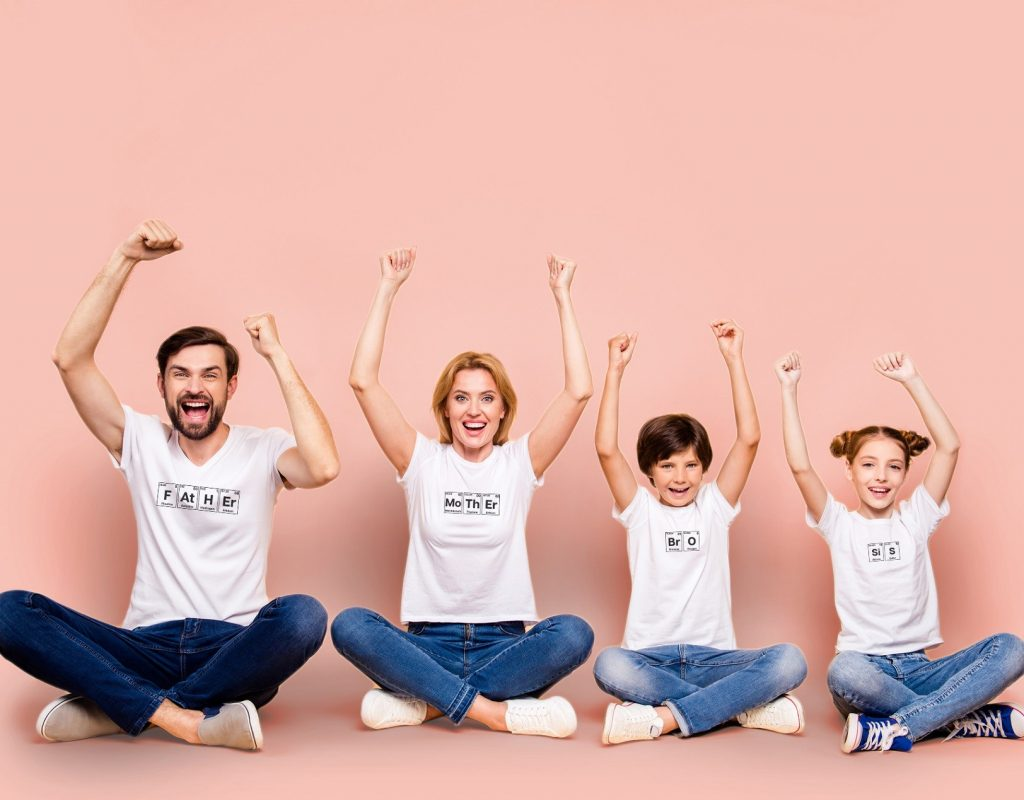Young smiling family, bearded father, blonde mother, little boy and girl wearing blue jeans and white T-shirts, sitting in odrer of hierarchy in lotus pose raising up hands